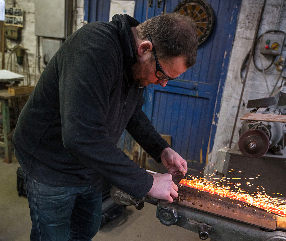 Stuart Mitchell sharpening a blade in his workshop