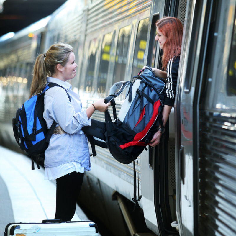 A woman passing a backpack to a friend on the door of a train at a railway station